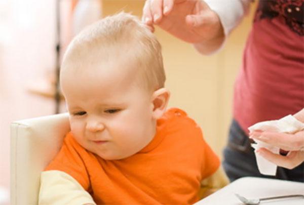 Маленькому ребенку мама пытается втереть масло в волосы, а он отворачивается