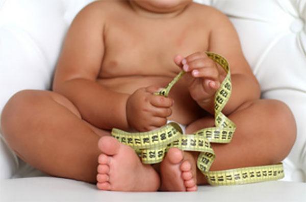 Ребенок с ожирением держит в руках сантиметровую ленту
