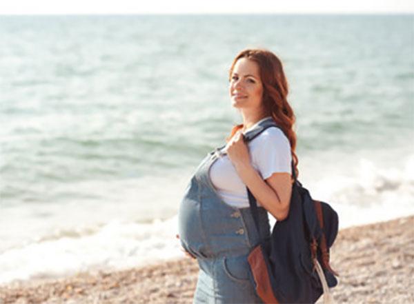 Беременная женщина ходит по берегу моря