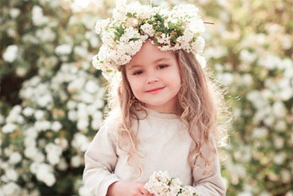 Трехлетняя девочка с красивым венком из цветов на голове