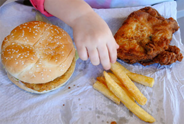 Гамбургер, картошка фри, к которым тянется ручка ребенка