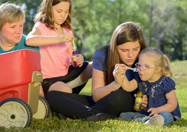 Девочка с умственной отсталостью надувает пузыри. Рядом мама,, сестра и бабушка