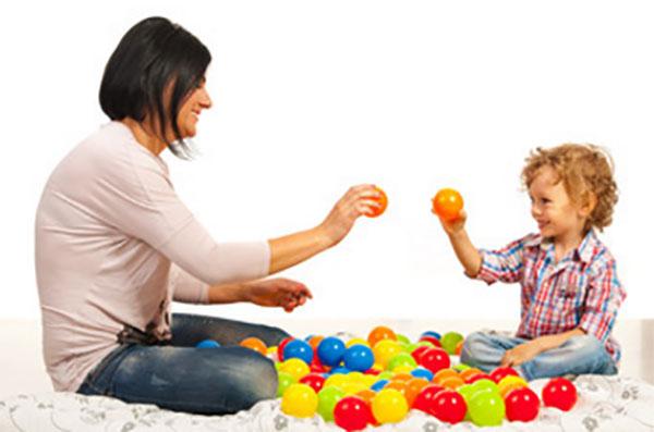 Мама с сыном сидят на полу, между ними разноцветные мячики