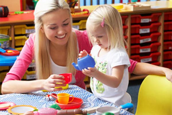 Мама с дочкой играют игрушечной посудкой