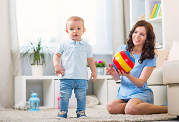 Мама держит мяч, рядом стоит ее маленький сын