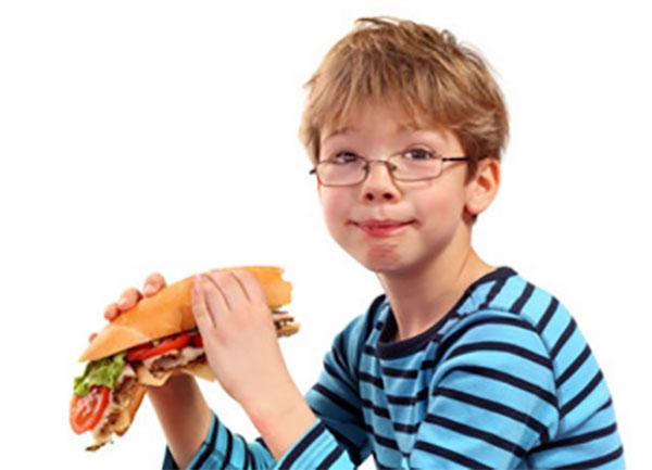 Мальчик держит в руках большой сендвич