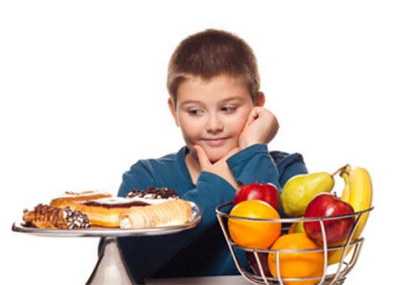 Мальчик смотрит на сладости, рядом емкость с фруктами