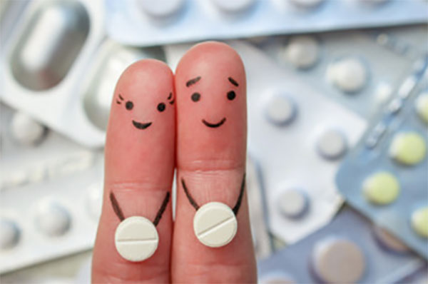 На заднем плане пластинки с таблетками. На переднем - два пальца, на каждом по таблетке и нарисованы мордочки