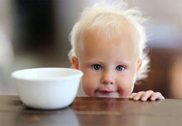 Годовалый мальчик стоит возле стола, на котором стоит миска