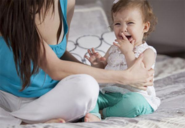 Мама смидит рядом с плачущим ребенком