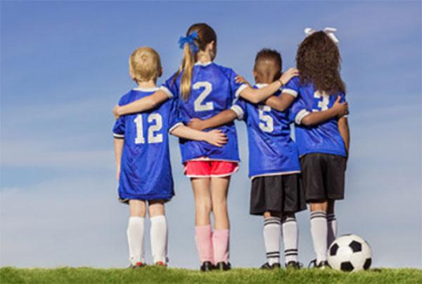 Дети в футбольной форме, рядом футбольный мяч