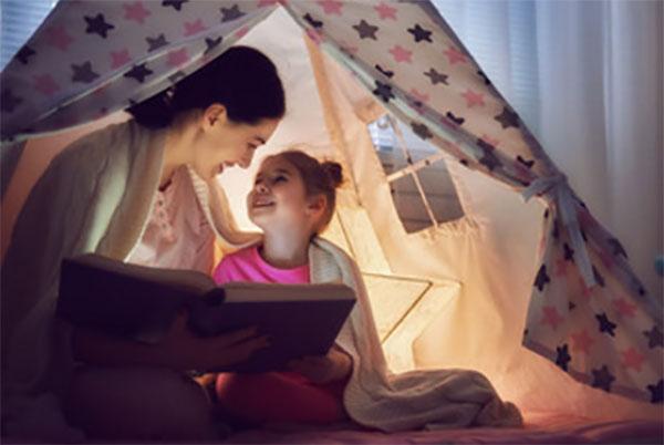 Мама с дочкой читает книгу в палатке