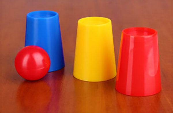 Синий, желтый и красный стаканы, перевернутые вверх ногами, и красный шарик