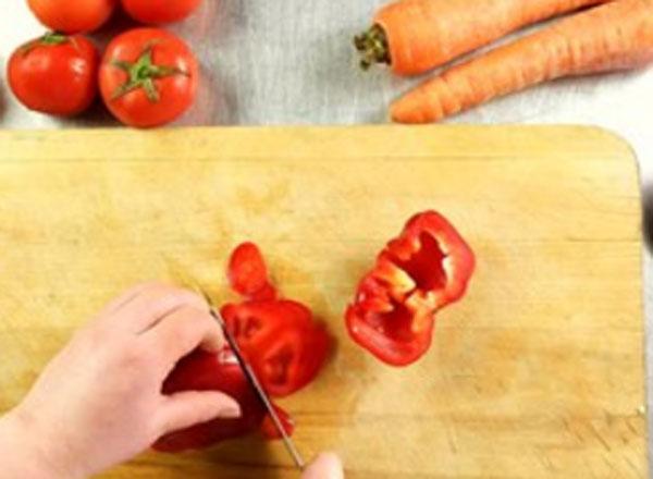 Нарезание болгарского перца. Рядом с досточкой лежат помидоры и морковки