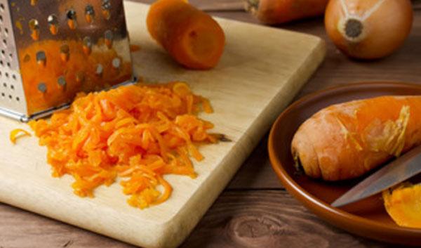 Отварная морковь, частично натертая на терке, терка и миска с неочищенными овощами