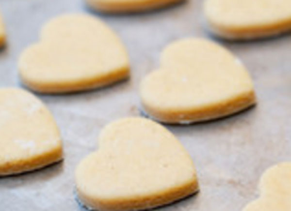 Сырое печенье в форме сердца на противне
