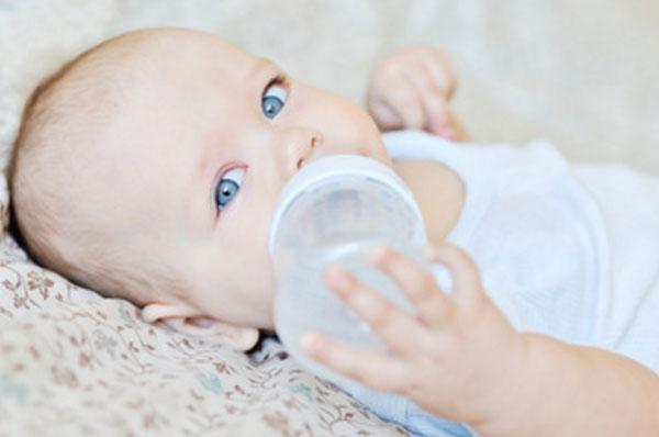 Грудной ребенок пьет воду с бутылочки