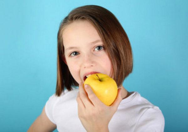 Девочка грызет яблоко