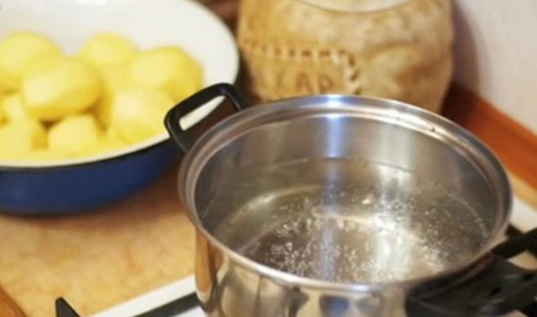 Закипает вода в кастрюле. на заднем плане в миске очищенная картошка