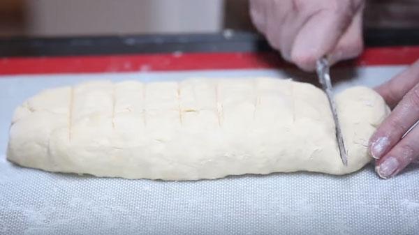 Колбаску из теста разметили на девять кусков, начинают первый отрезать