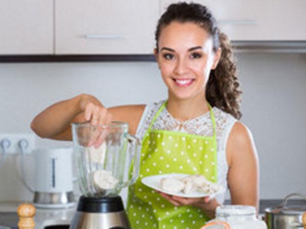 Женщина кладет ингредиенты в блендер