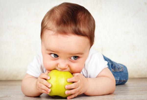 Грудной ребенок пытается укусить яблоко, лежа на полу