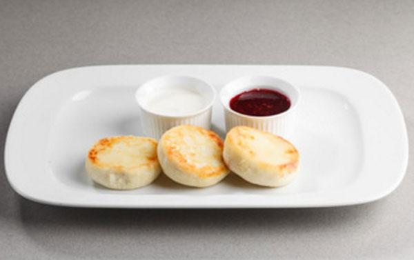 На тарелке готовые сырники. Рядом две маленьких тарелочки. Одна со сметаной, другая с ягодным соусом
