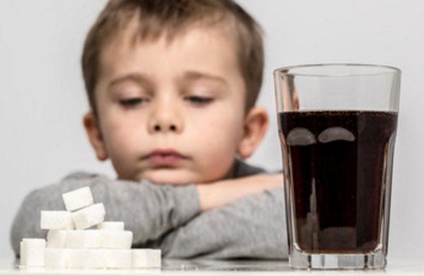 Сидит расстроенный мальчик. Перед ним стакан чая и сахар рафинад