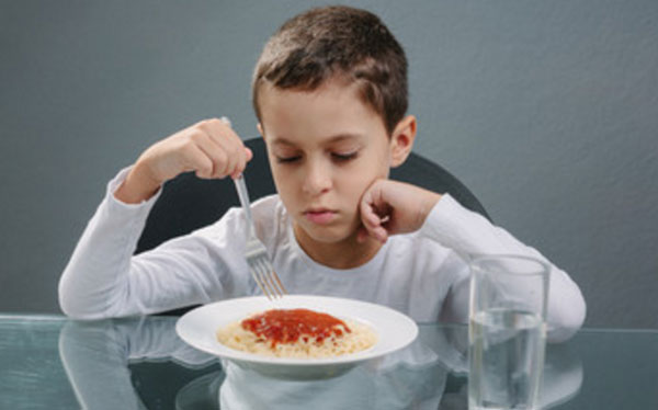 Мальчик нехотя ковыряется в тарелке