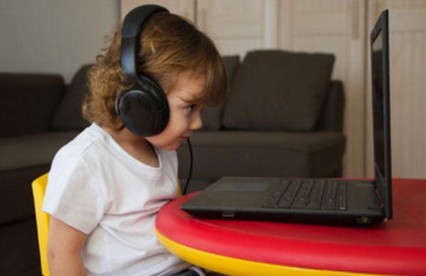 Ребенок неровно сидит перед ноутбуком
