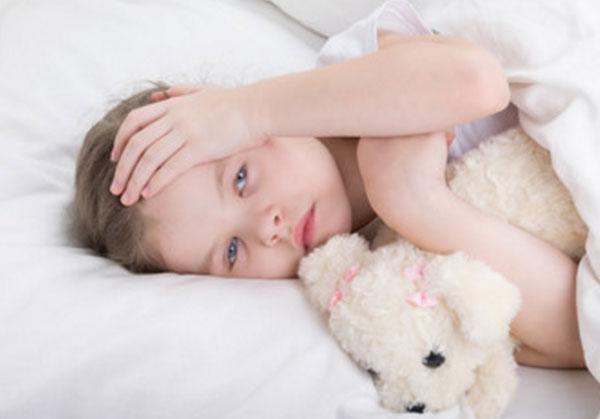 Болезненный ребенок лежит в постели, держится за голову