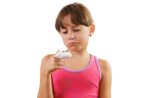 Грустная девочка с забинтованным указательным пальцем