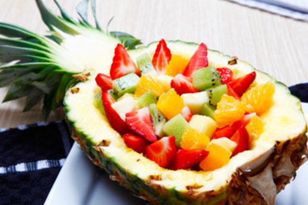 Половинка ананаса, заполненная фруктовым салатом