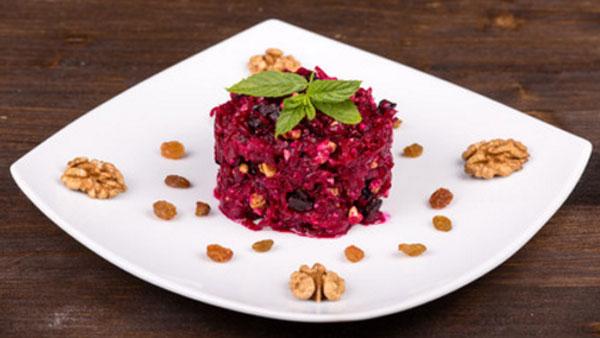 Блюдо с готовым салатом, украшенное грецкими орехами и изюмом
