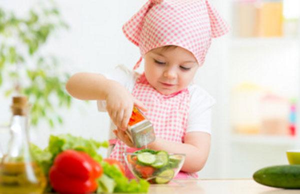Маленькая девочка в косынке и фартуке готовит овощной салат