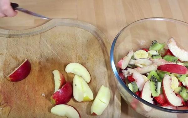 Яблоко нарезано на дольки, лежит на достояке. Рядом мисочка с остальными ингредиентами салата