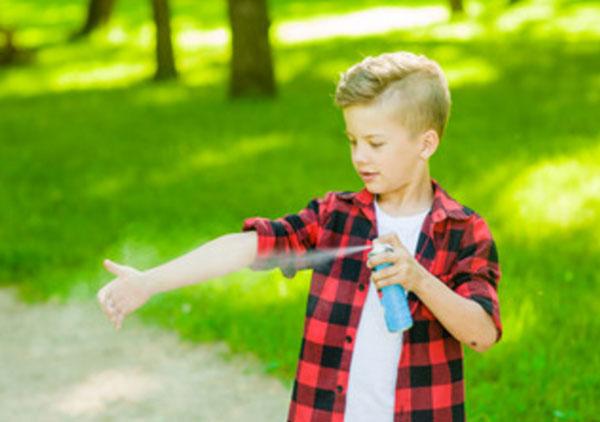 Мальчик распрыскивает репеллент на свою руку