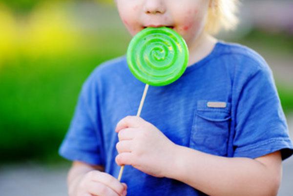Ребенок облизывает конфету на палочке. У него сыпь на лице