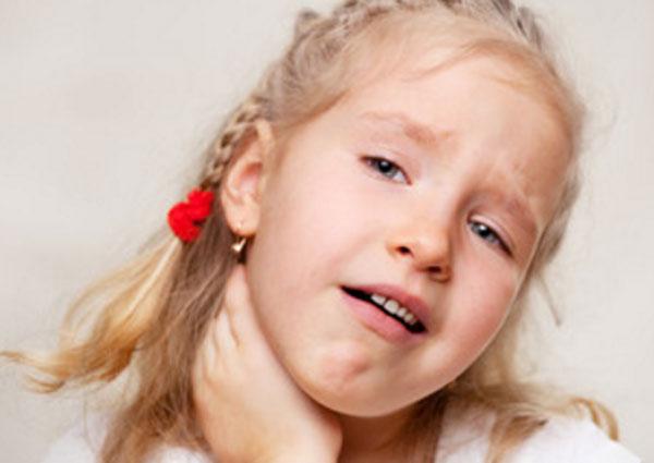 Девочка держится за горло. Ей больно