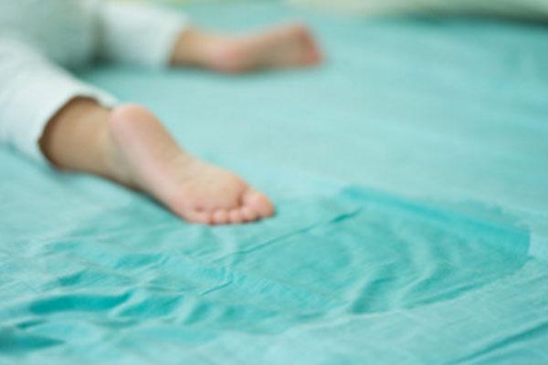 Ножки ребенка. рядом записянная простынь