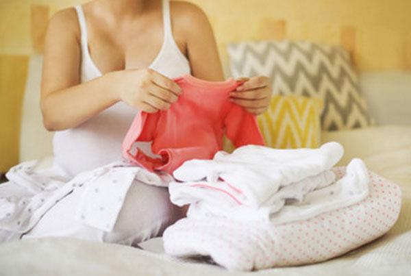 Беременная женщина складывает одежду для новорожденного