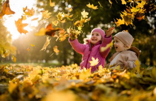 Дети на улице. Играют в куче листьев