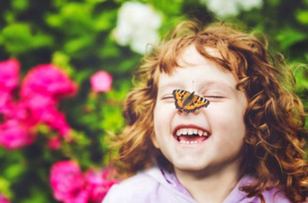 Девочка на улице рядом с цветами. У нее на носике сидит бабочка