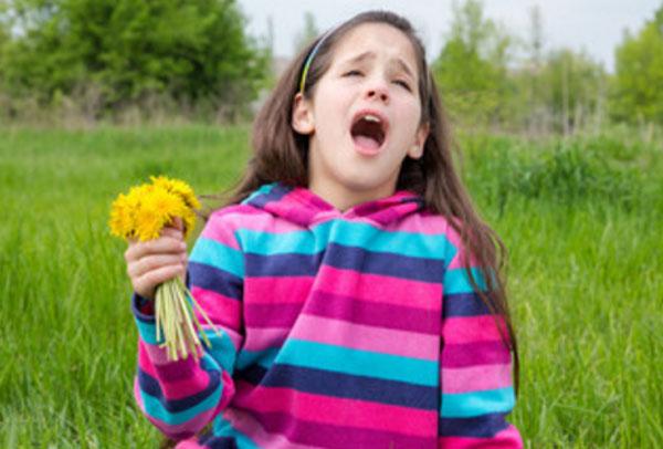 Девочка с открытым ртом. В руках держит букет одуванчиков