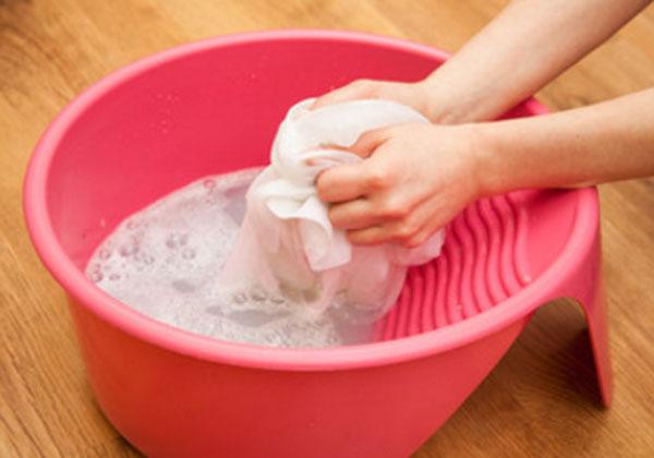 Женщина стирает руками в миске