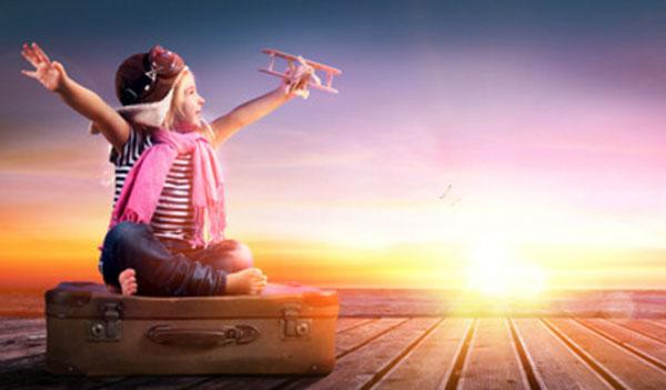 Ребенок в шапочке пилота сидит на чемодане и держит самолетик в руке