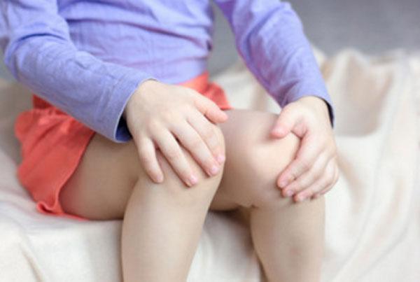 Малыш держится за колени