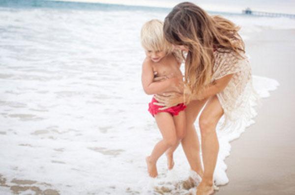Мама стоит с ребенком у самого берега, вода покрывает ноги