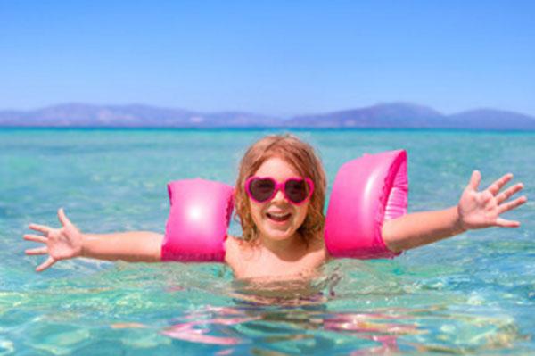 Счастливая девочка в воде с нарукавниками и в солнцезащитных очках