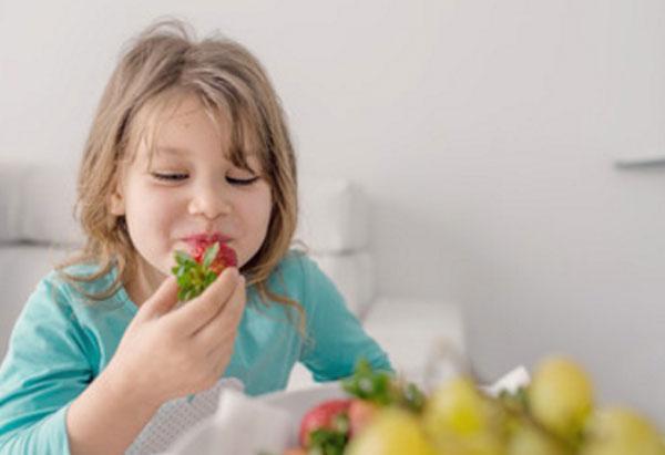 Девочка ест клубнику. На столе виднеются фрукты